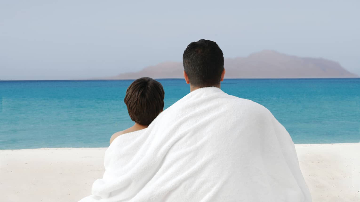Father and son share white towel drapes across backs, look out at beach and sea