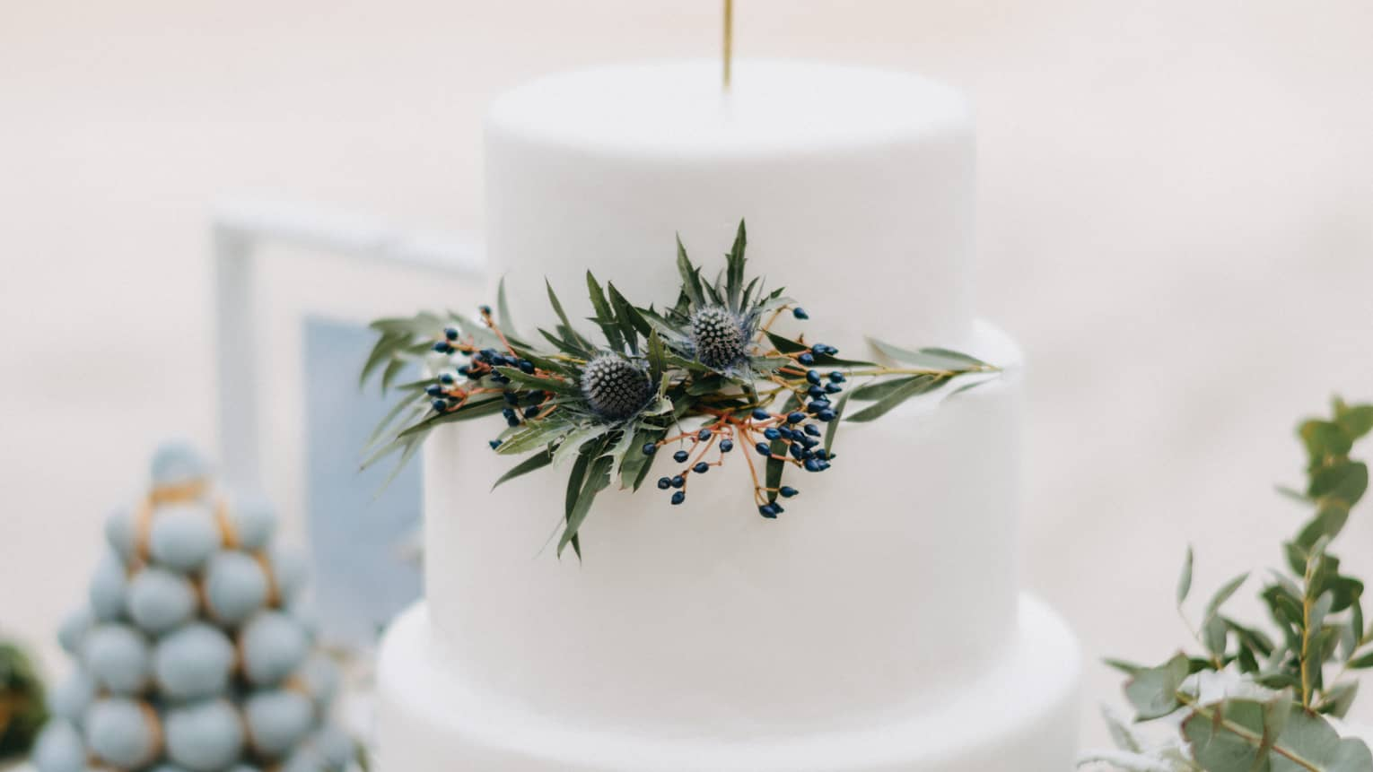 Three tiered wedding cake decorated with green leaves, white flowers