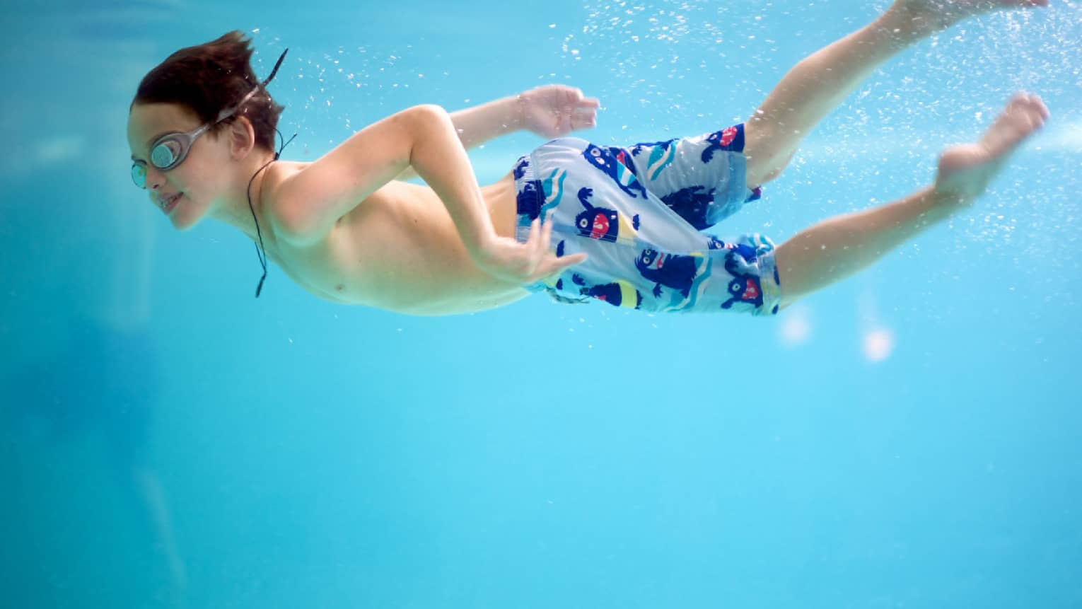 Underwater shot of a boy swimming in a pool with goggles and swim trunks
