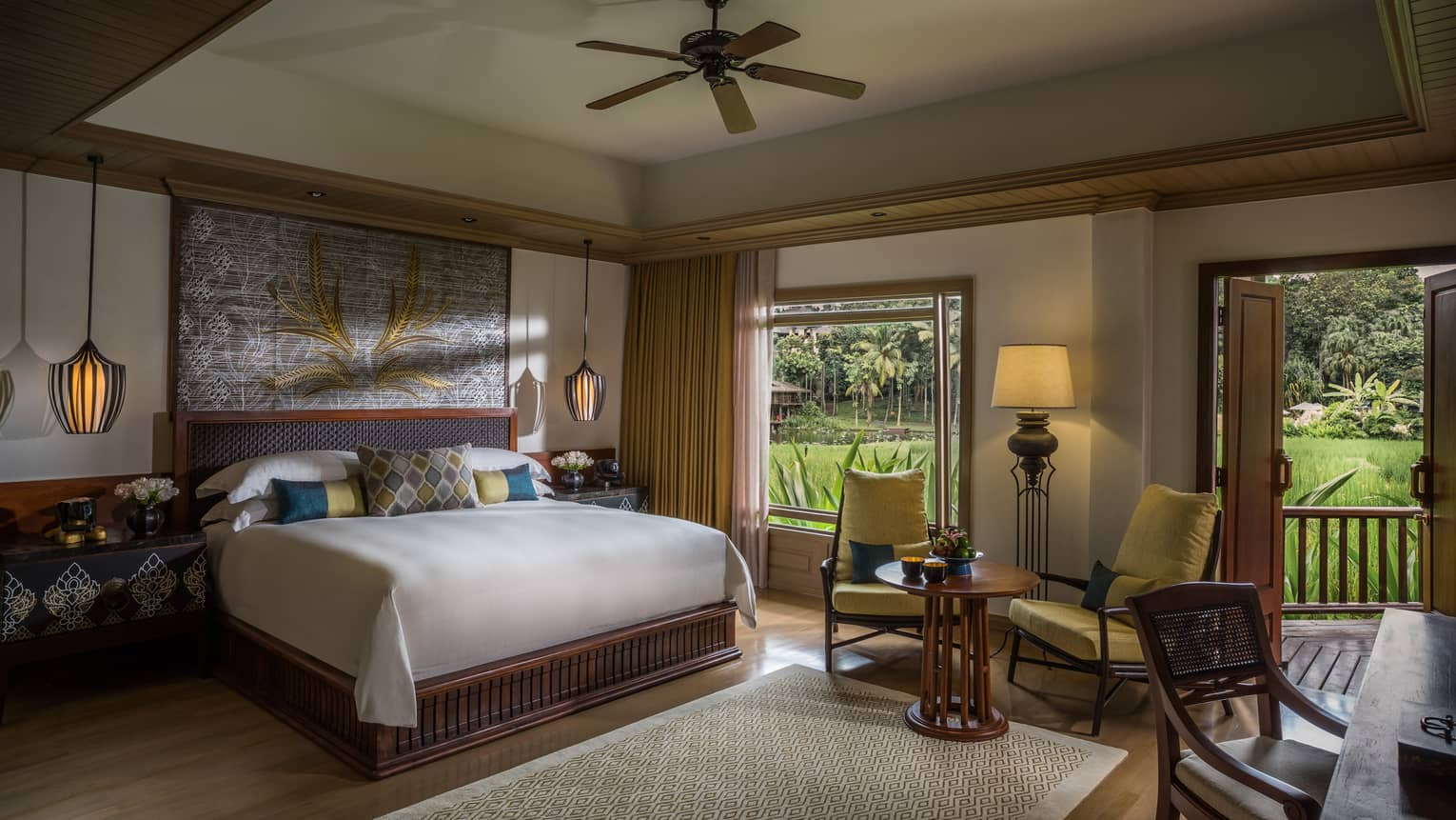 Rice Terrace Room bed with blue, gold accent pillows under painting, table by window with plantation view