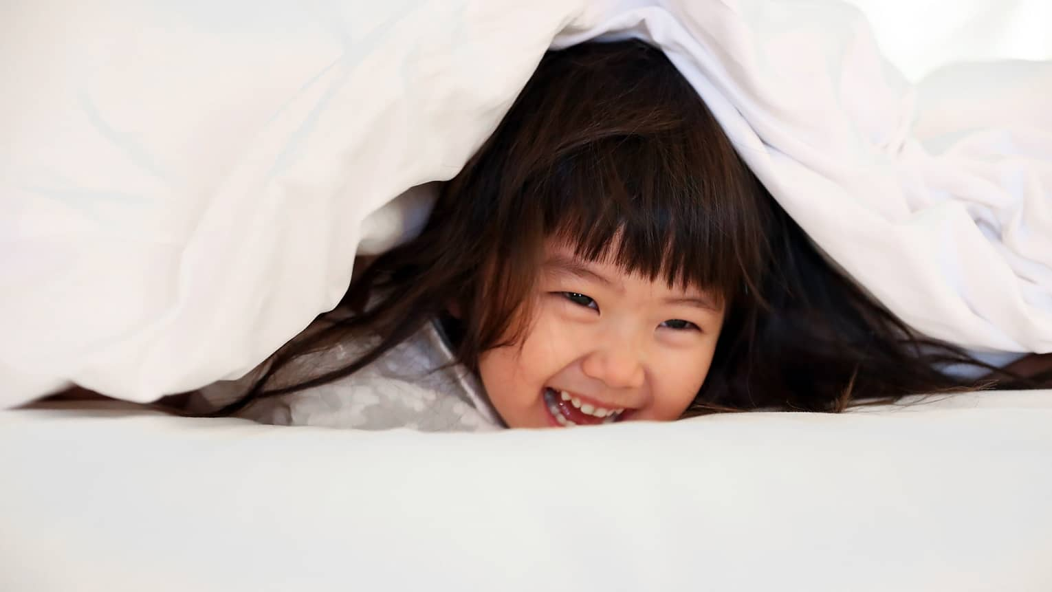 Young girl laughing as she plays under a white bed sheet