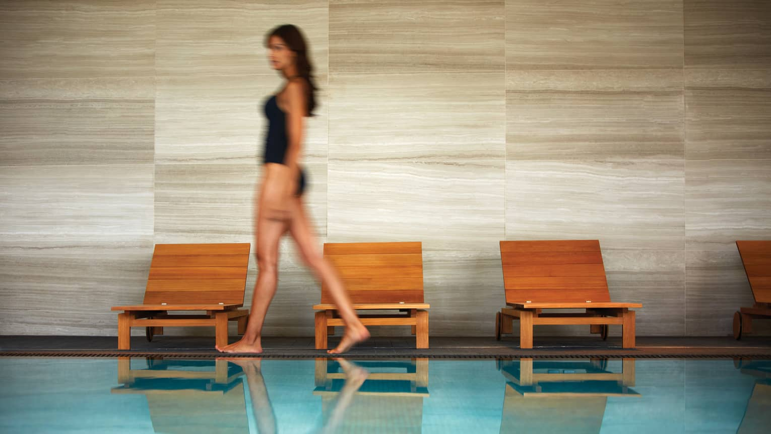 Blurry image of woman in black swimsuit as she walks by wood lounge chairs on pool deck