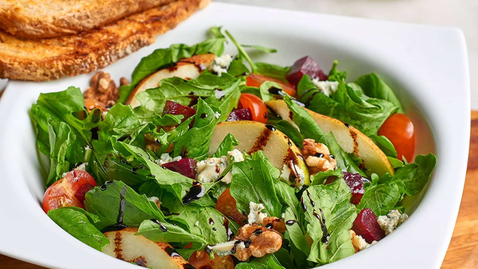 Salade Parisienne dish with green lettuce, grilled chicken slices, tomato, crumbled goat cheese