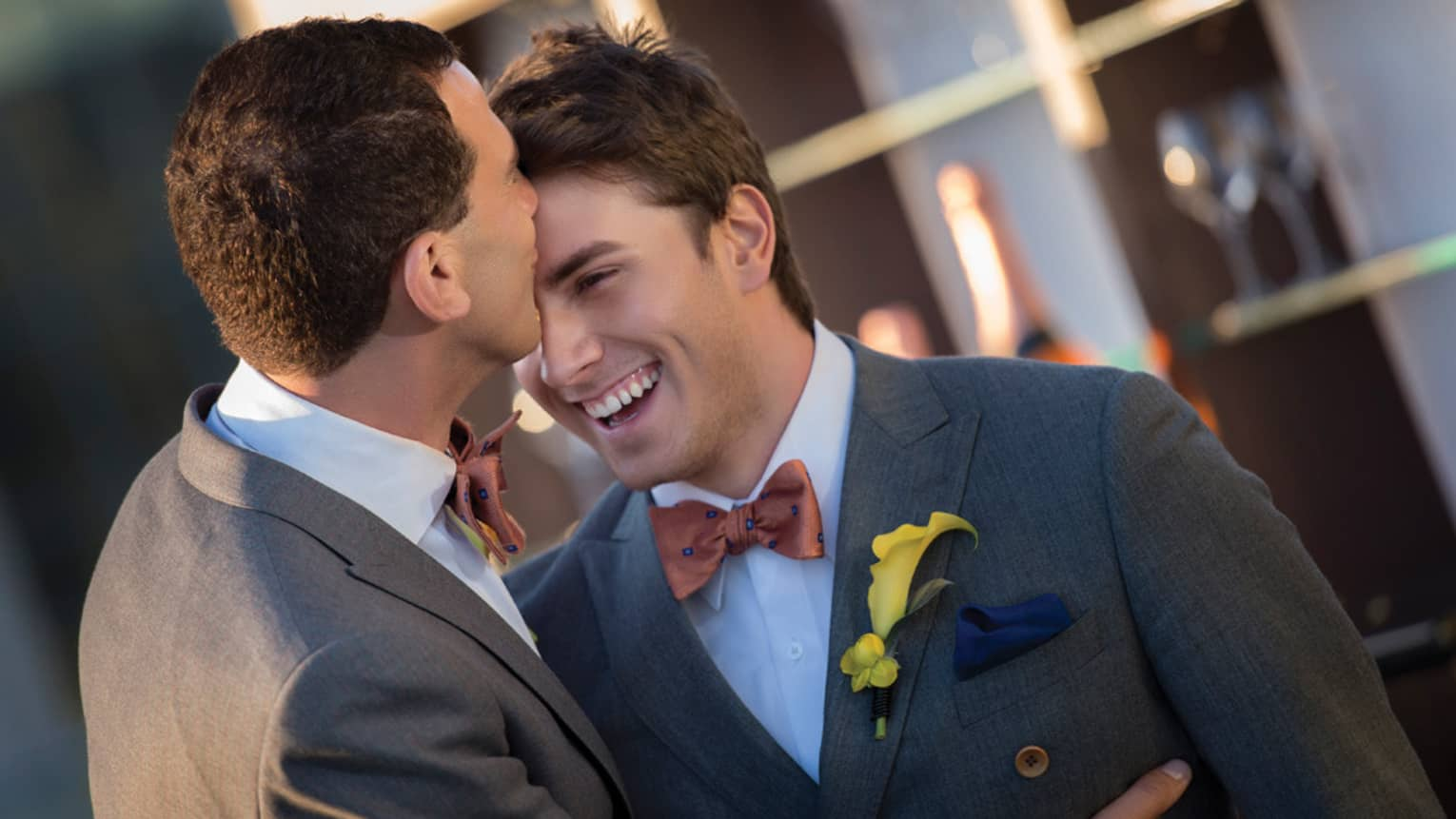 Two grooms wearing matching tuxedos, one kisses the other's forehead