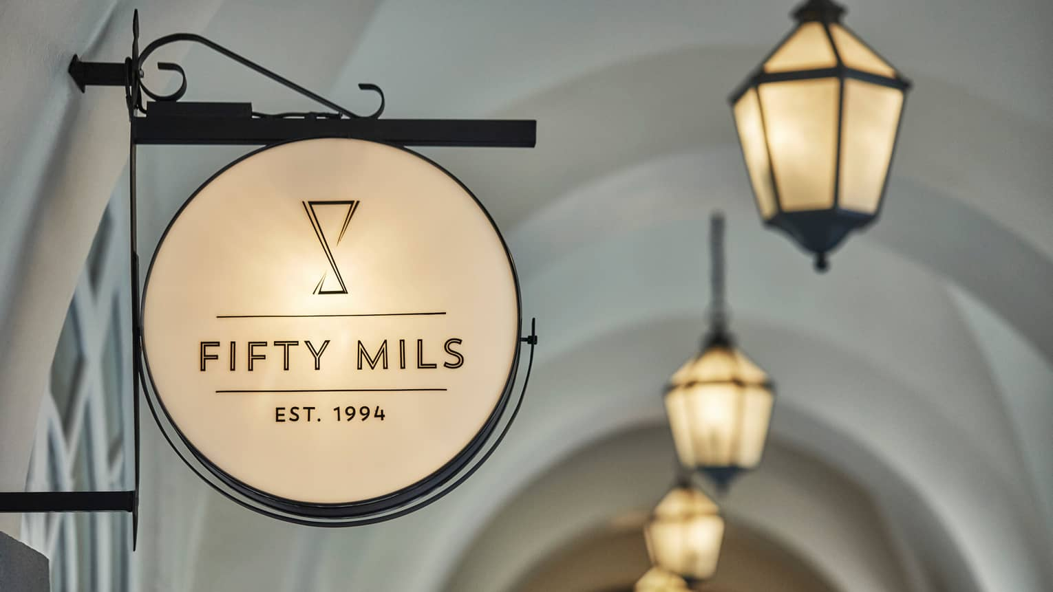 Close-up of round sign with lounge sign reading Fifty Mils Established 1994, lanterns
