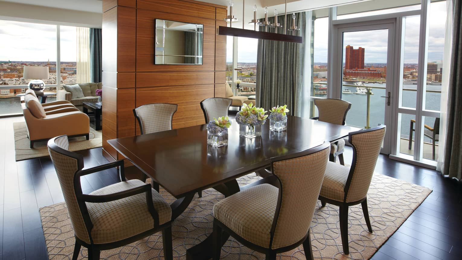 Serene Suite dining table for six, adjoining living room, glass walls with harbour view