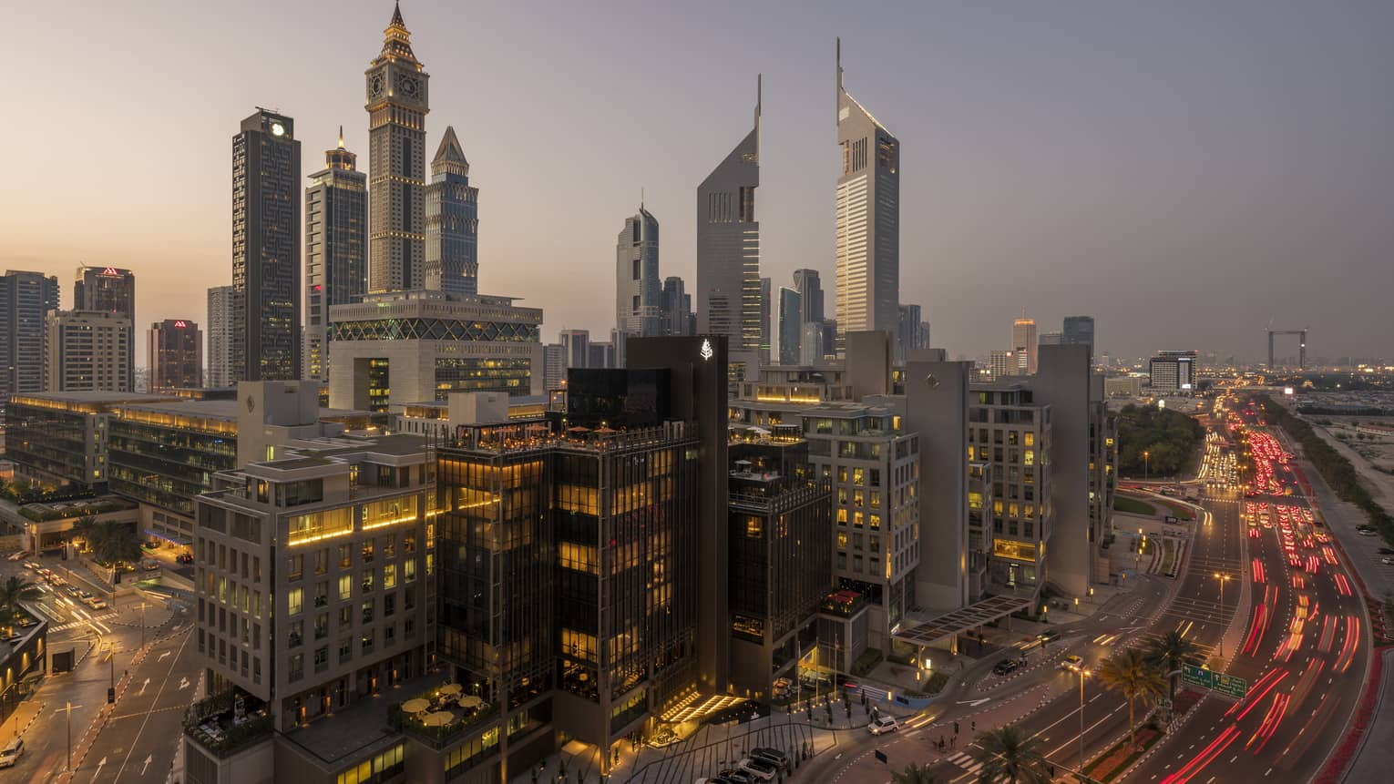 Aerial view of Dubai city skyline, road, lights around Four Seasons International Financial Centre hotel at sunset