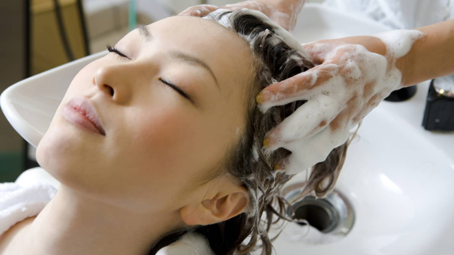 Woman closes eye and leans back against sink as hands massage shampoo into her scalp