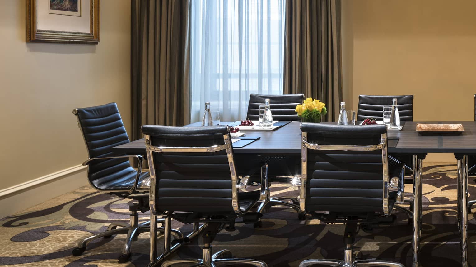 Long boardroom meeting table with leather swivel chairs