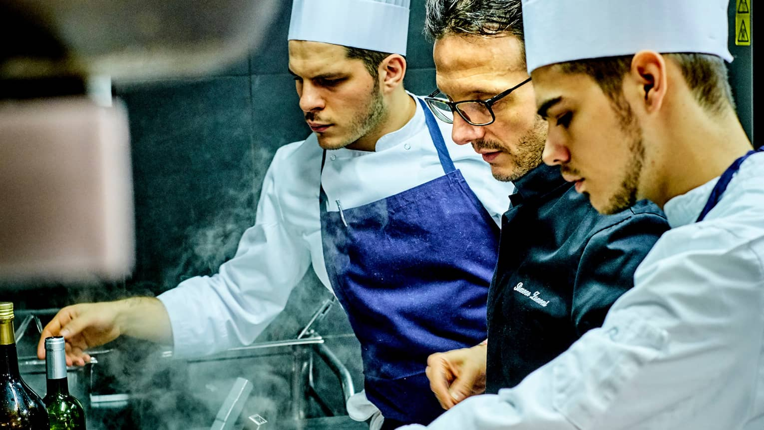Chef Simone Zanoni and team look over stove