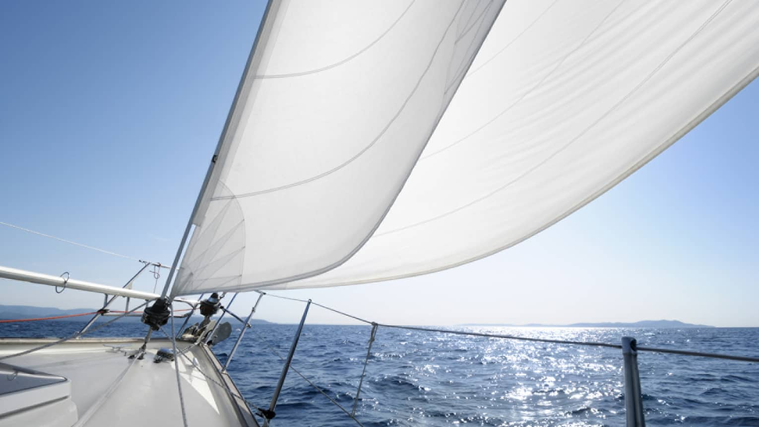 Close-up of white sails on yacht, blue ocean in background