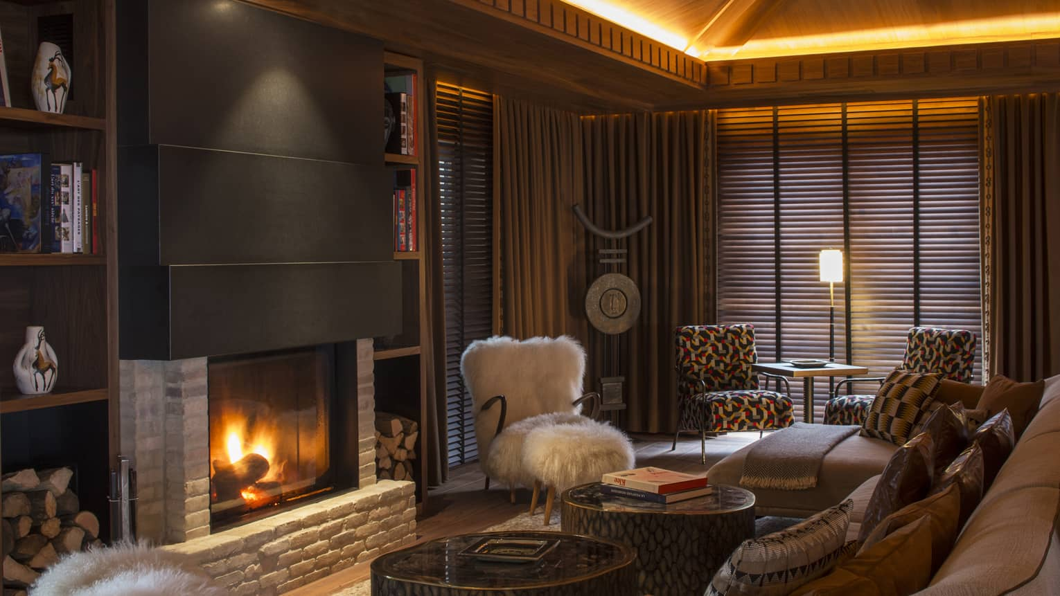 Large fireplace with stone and wood detail in cosy Lobby Lounge with brown tones