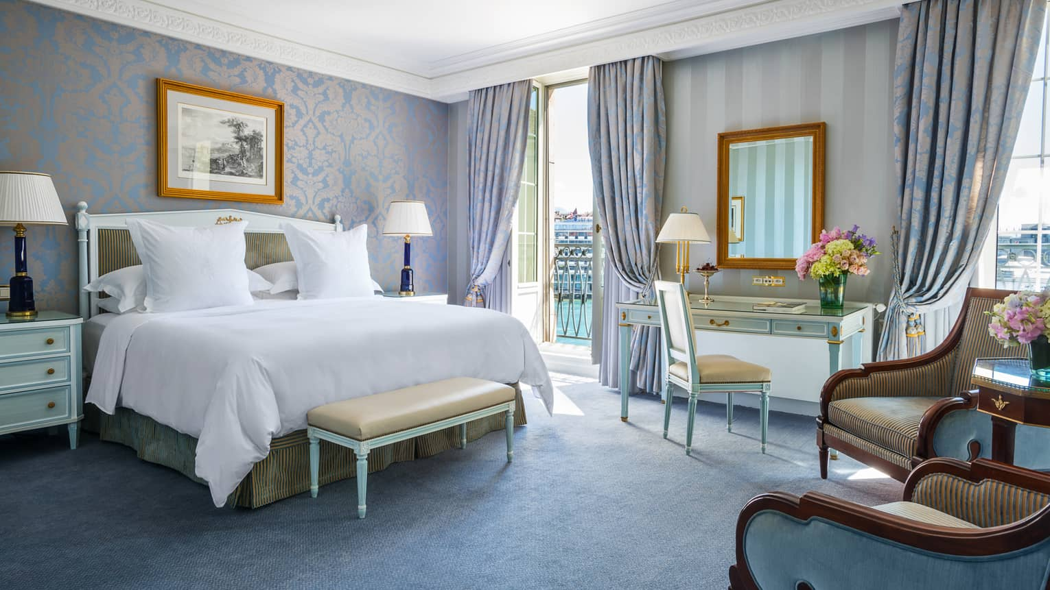 Deluxe Room bed with elegant blue-and-gold wallpaper and decor, floor-to-ceiling French doors opening to patio