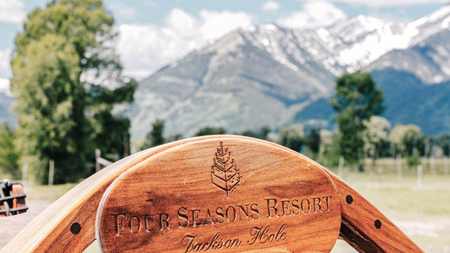 Close-up of the Four Seasons Jackson Hole logo engraved on a wooden plaque near the helm of a boat