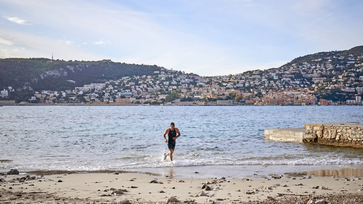 Man jogging in water toward sandy shore, hills in backdrop