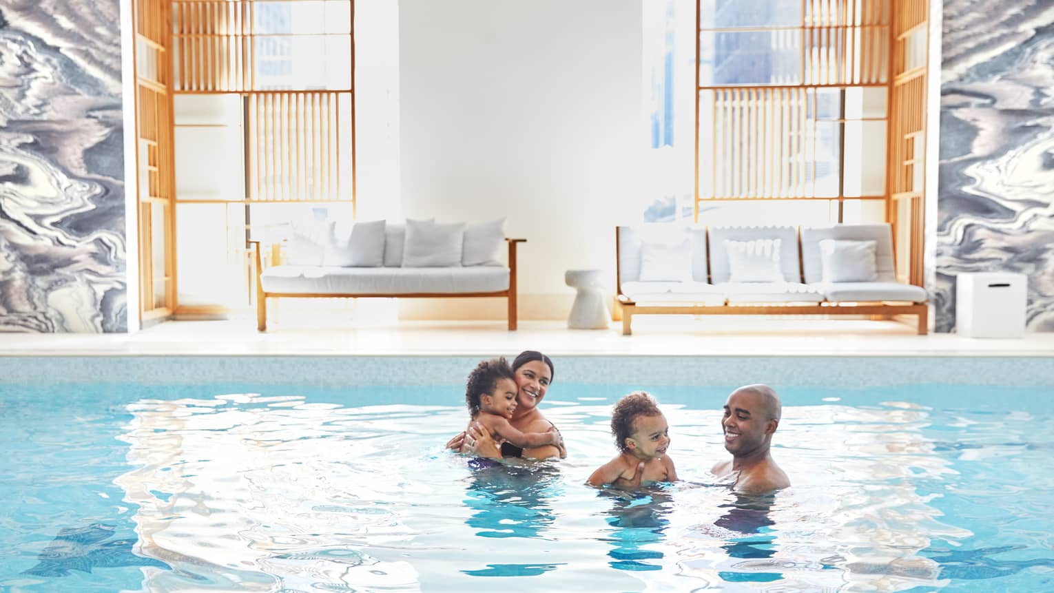 A family of four has fun in the indoor pool