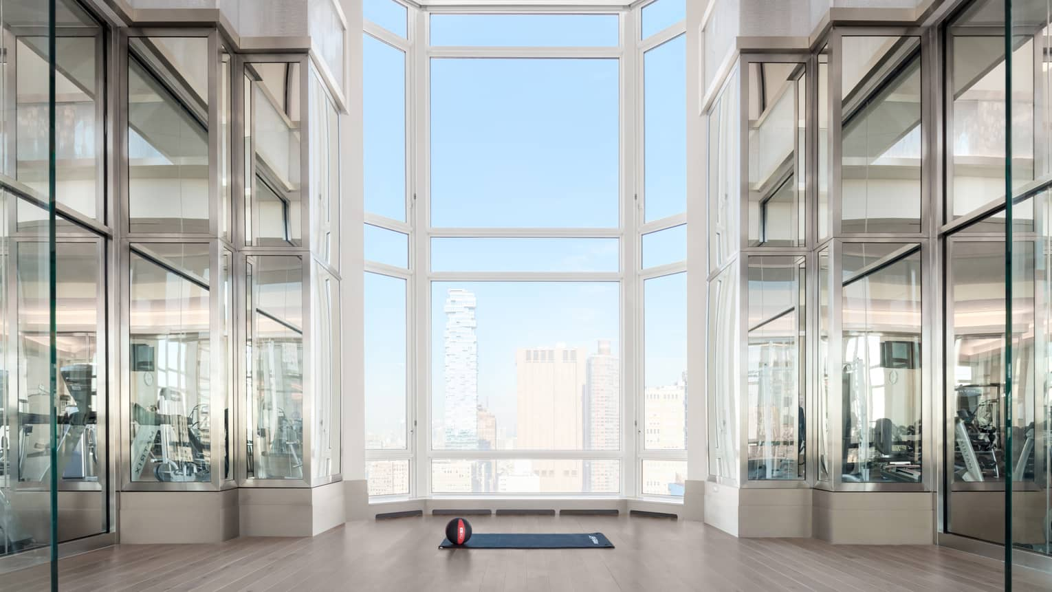 Basketball sits on yoga mat under soaring windows in modern Residential Fitness Centre overlooking Manhattan
