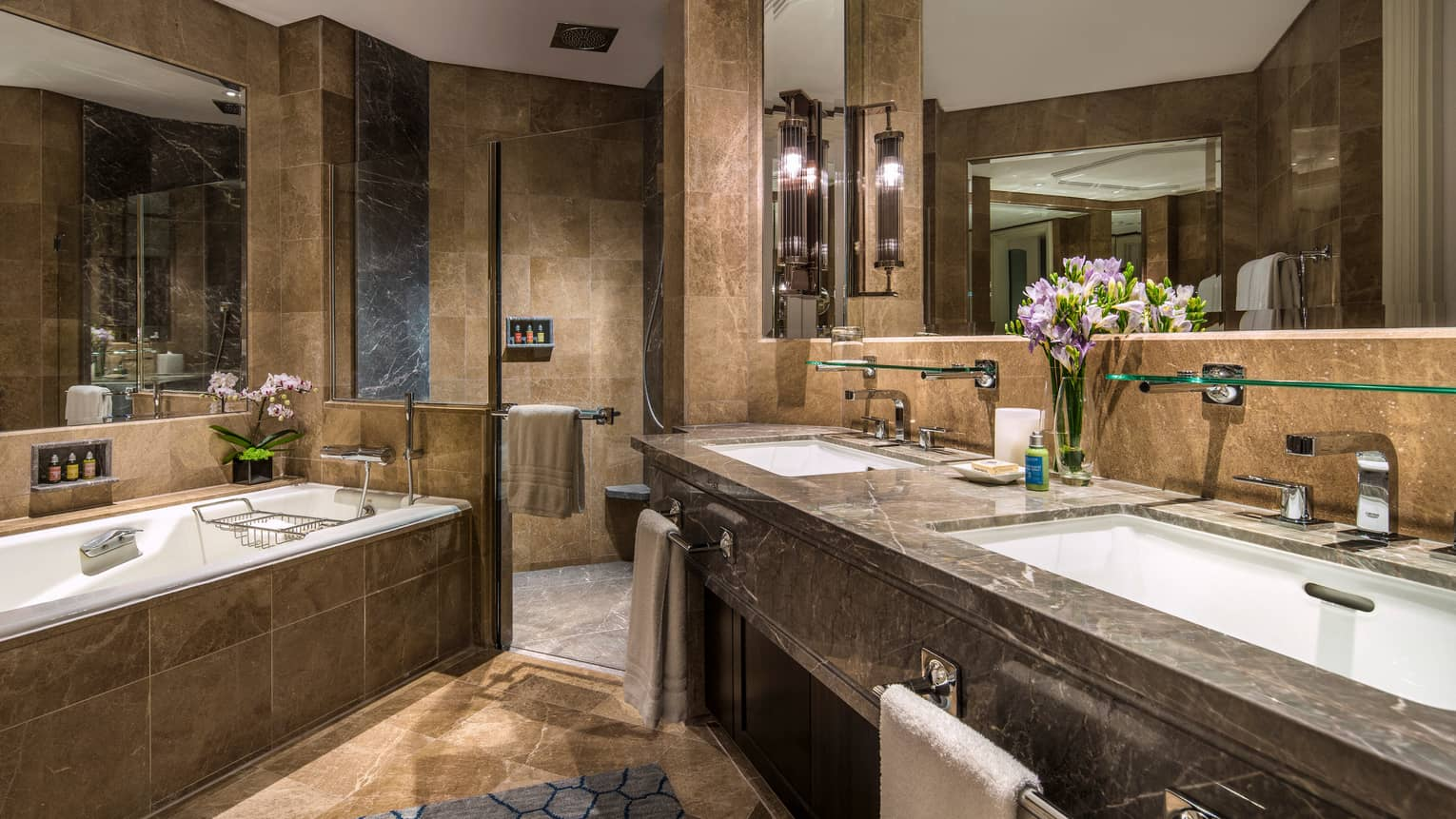 Brown marble bathroom with double vanity, large walk-in shower and soaker tub