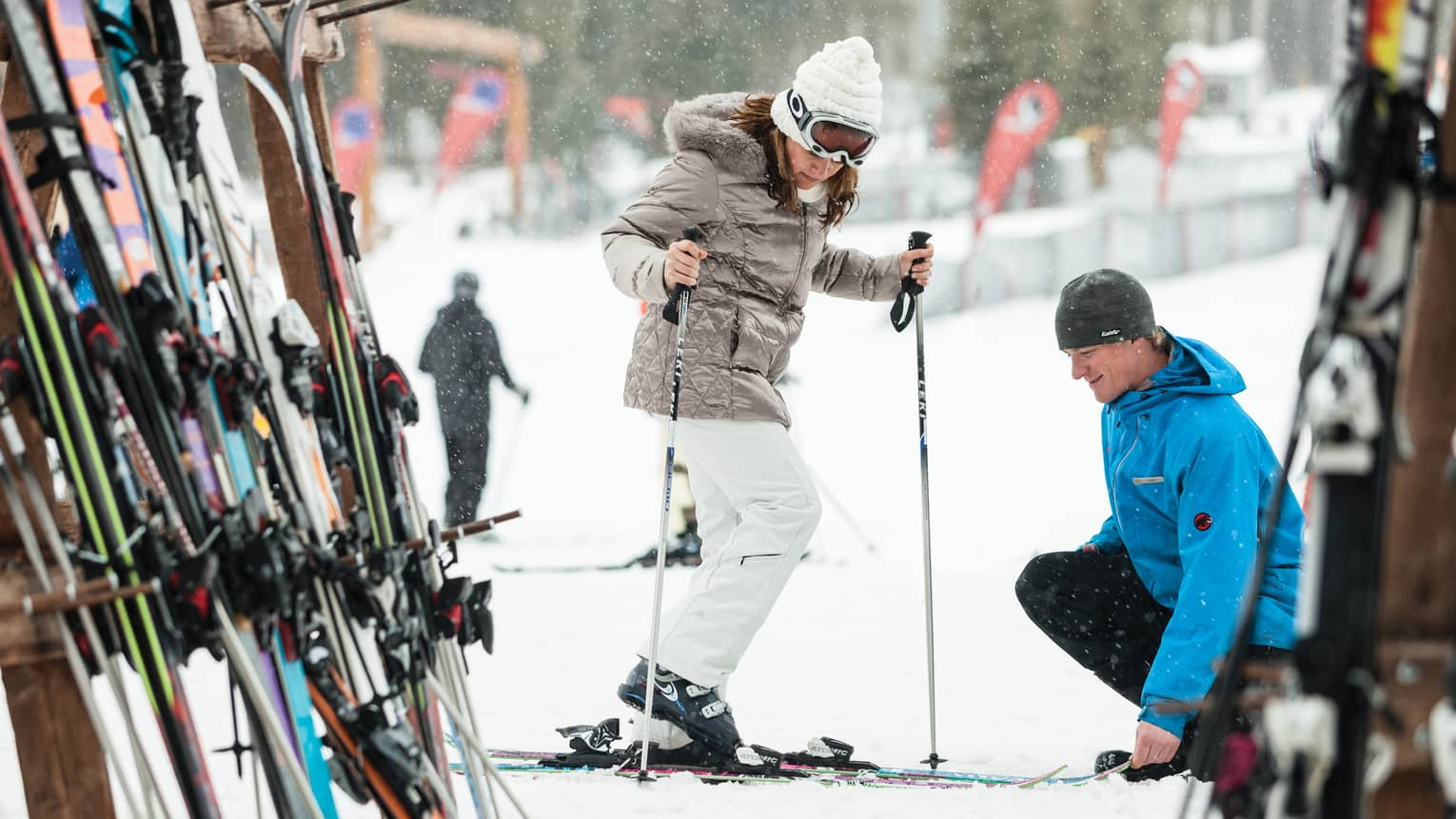 Ski concierge kneels down by woman trying on skis in front of rack