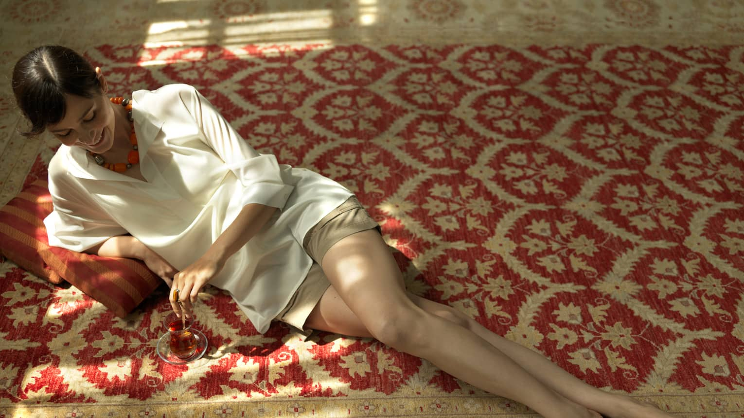Woman lies under sun on kilim carpet, pillow with glass of wine