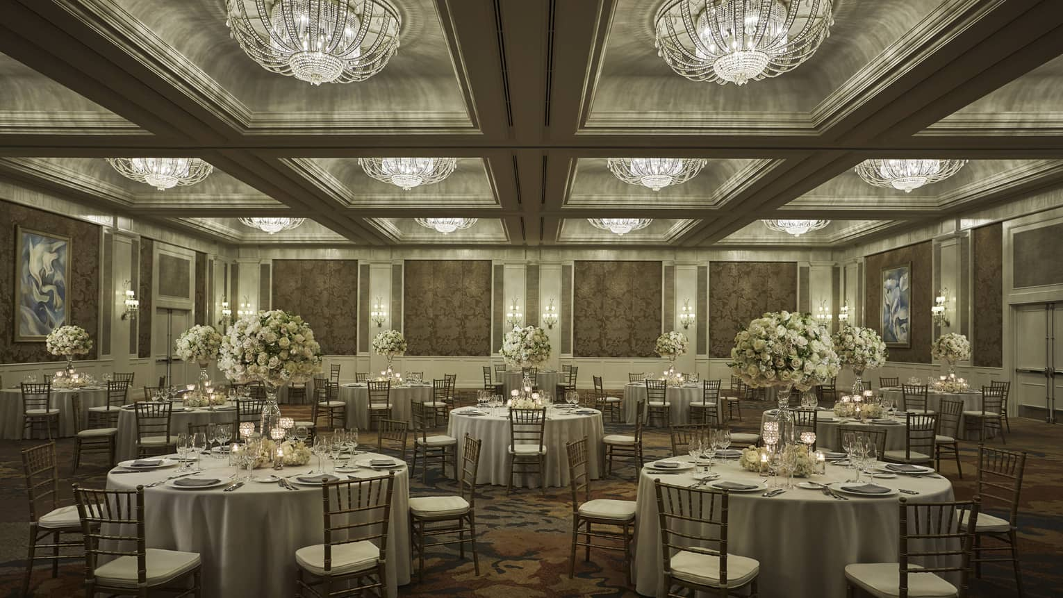 Round tables under crystal chandeliers in elegant Ocean Ballroom event space