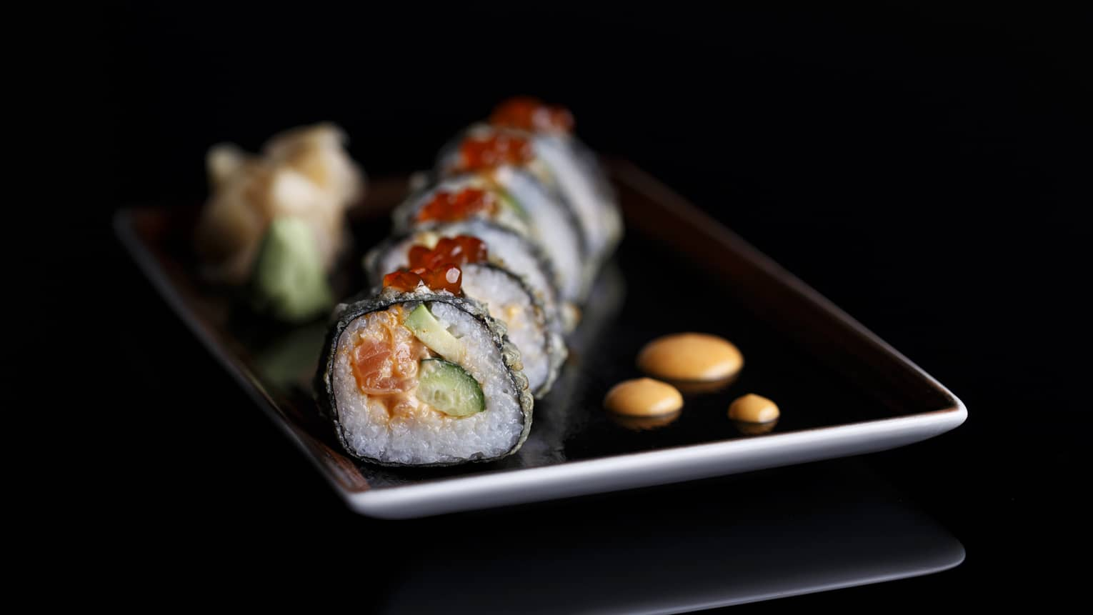 Handcrafted maki sushi roll with cucumber, salmon and avocado on black tray on shiny black table