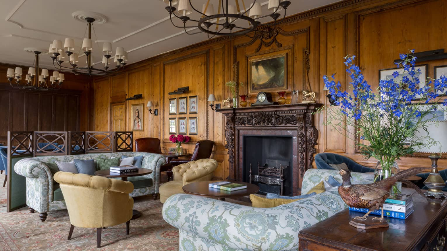 The Library, antique-style blue floral sofas, armchairs, rustic wood walls, soaring ceilings