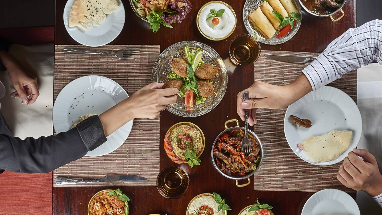 Aerial view of two people at dining table sharing hot and cold meze plates, Syrian and Lebanese meals