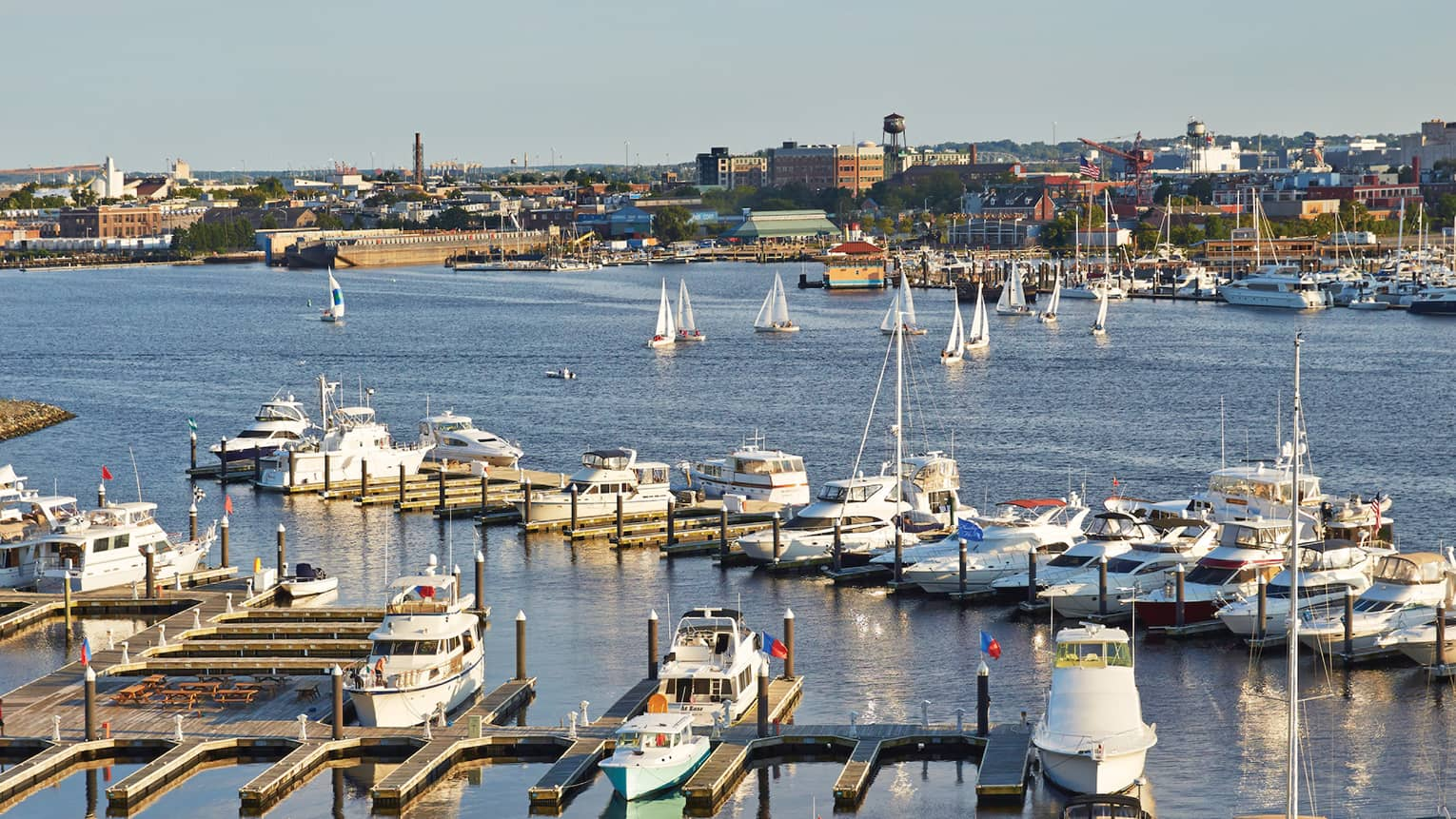 Looking down over boats, docks in Baltimore harbour on sunny day