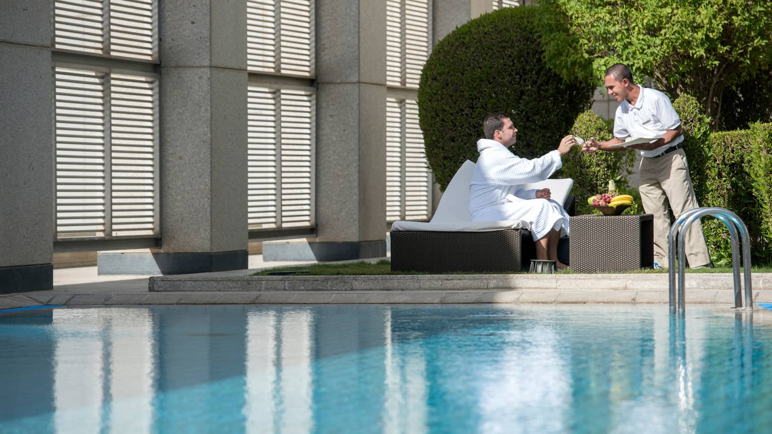 Man in white bathrobe sits on lounge chair on sunny swimming pool deck by fruit bowl, hotel stands hands him cloth
