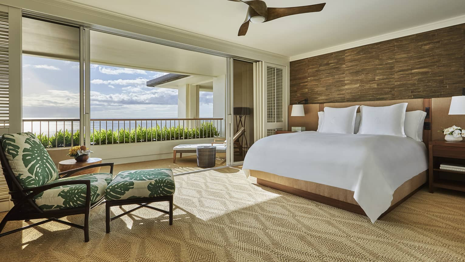 Hotel room bed and tropical print armchair by open air wall to patio, ocean view