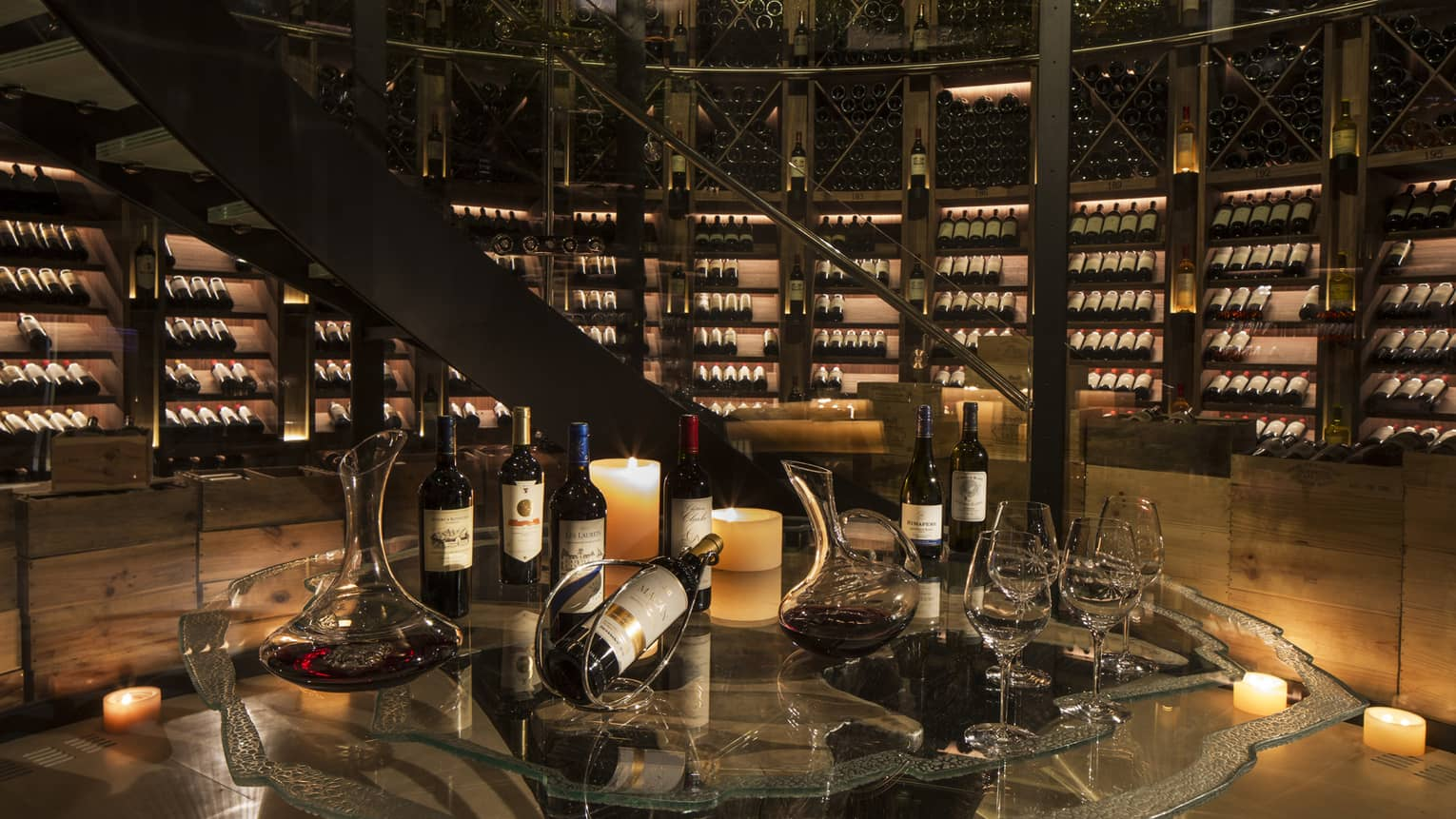 Bottles of wine are arranged for a tasting within an expansive, candlelit wine cellar