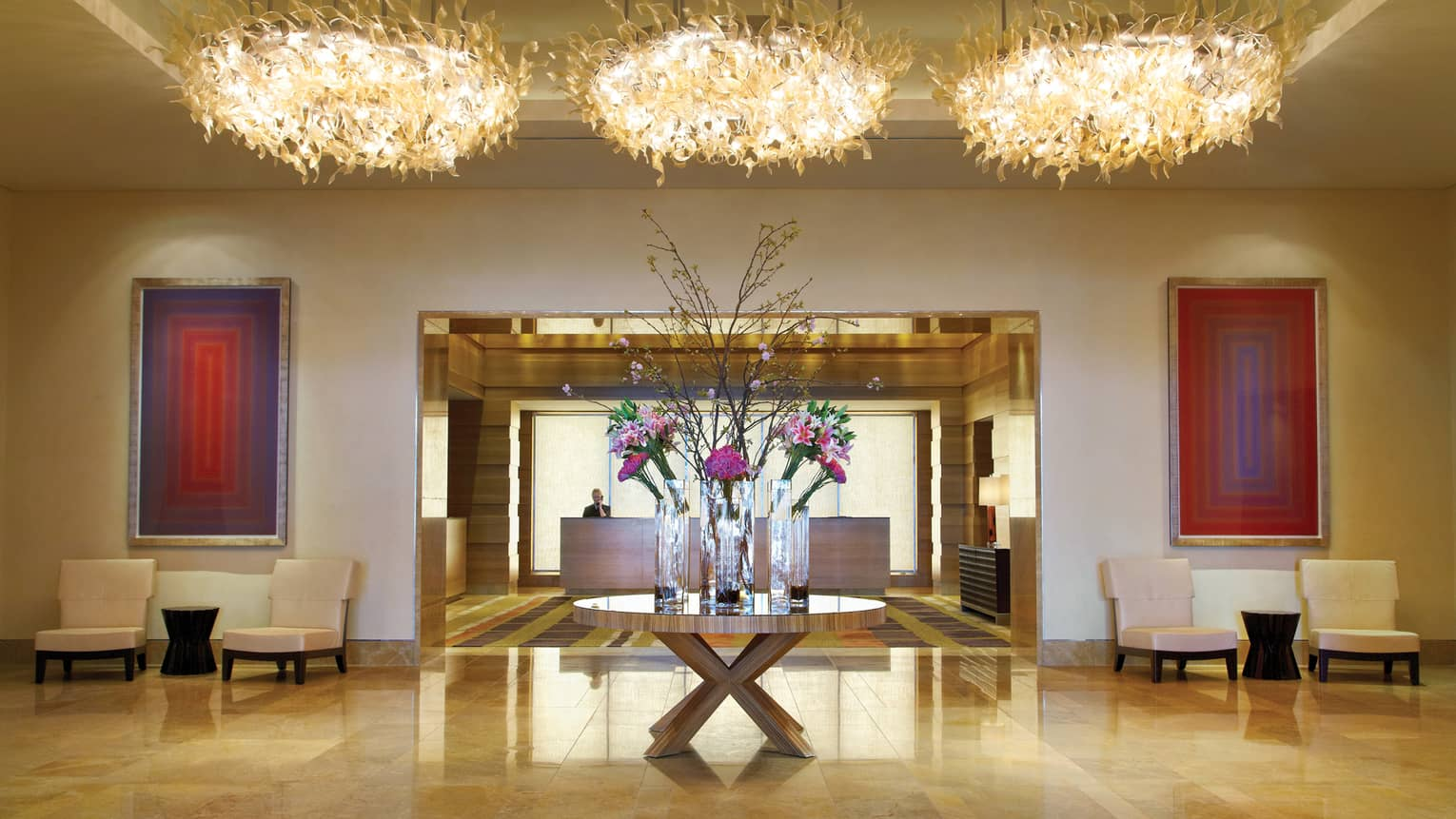 Three modern chandeliers hang above round table with vases, flowers in hotel lobby