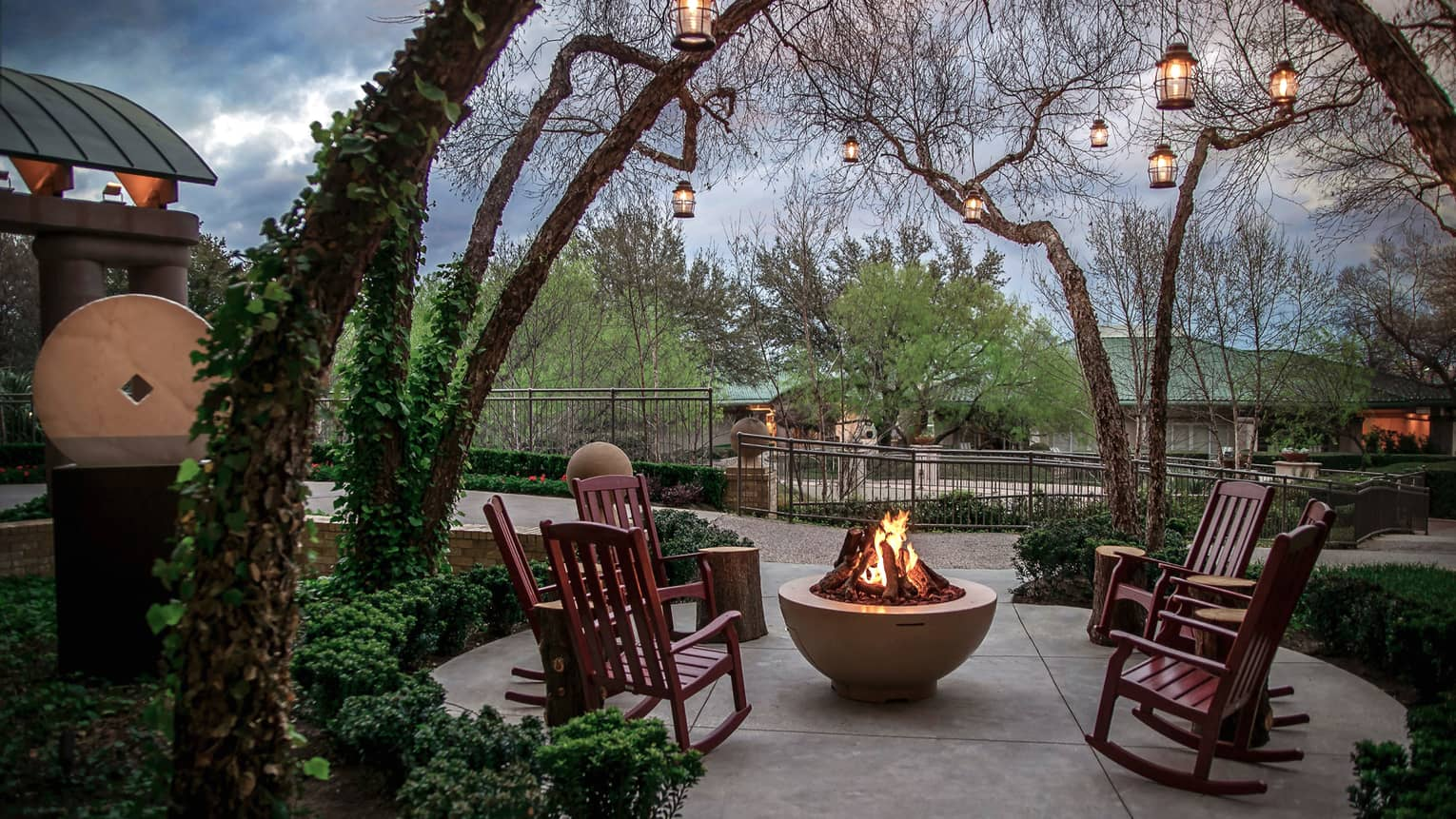 Wood rocking chairs around round outdoor fire pit under arched branches on Law restaurant patio