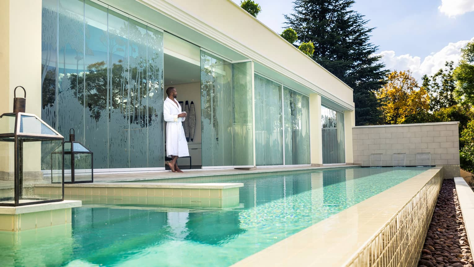 Man in white bathrobe stands between Spa glass windows on swimming pool deck
