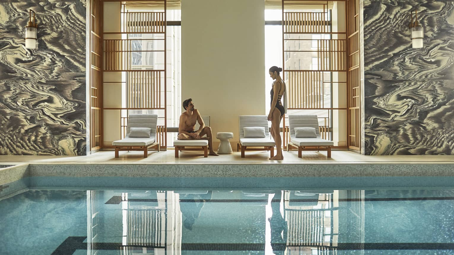 Man and woman in swimsuits by lounge chairs, window on indoor swimming pool deck