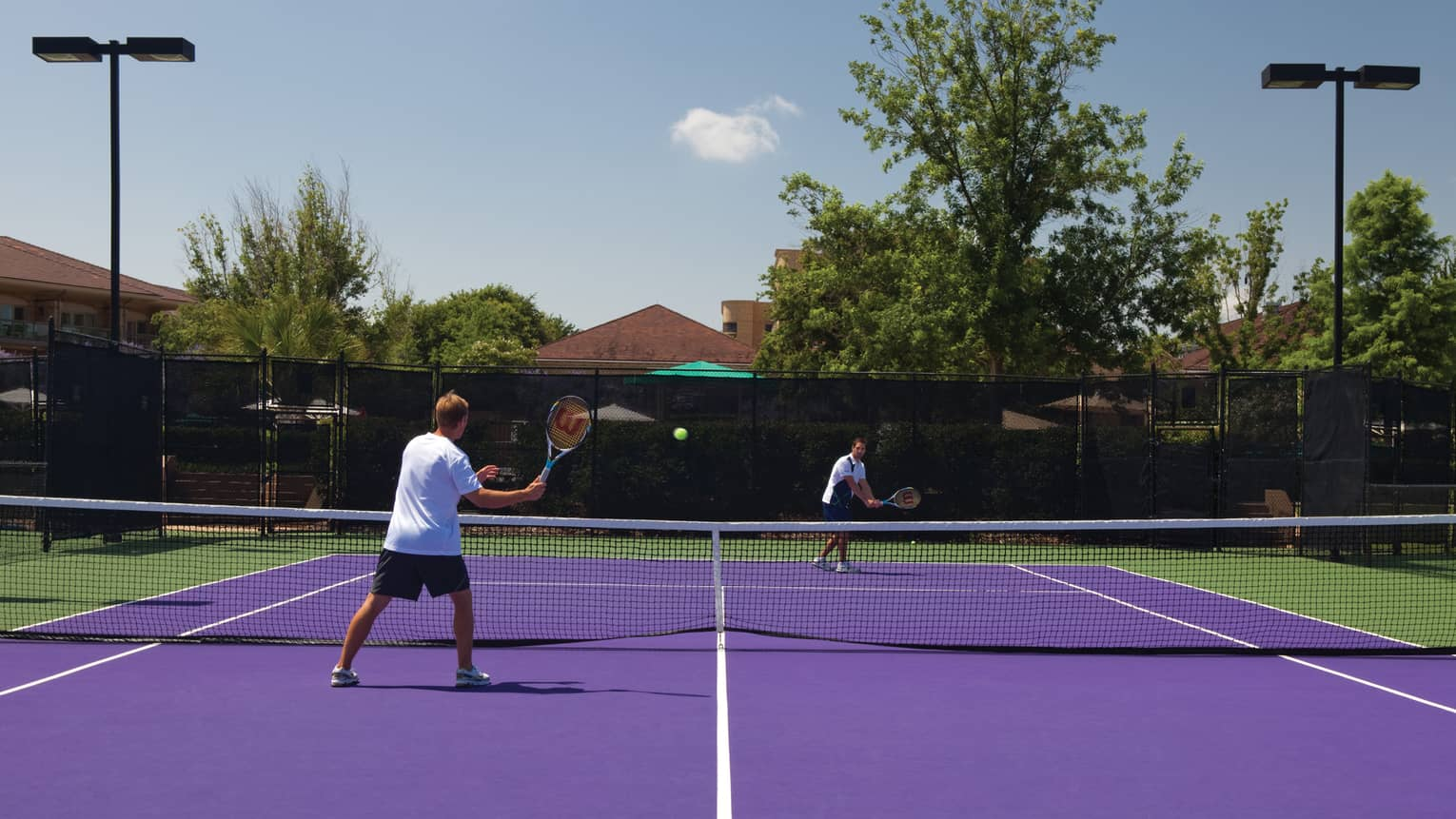 Two men play tennis game on purple court