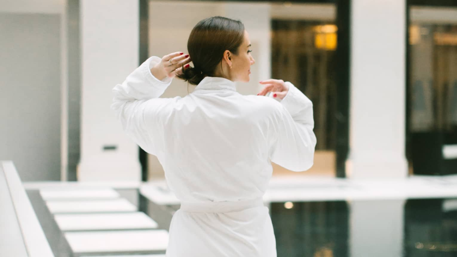 Back of woman wearing white spa robe walking across indoor swimming pool deck