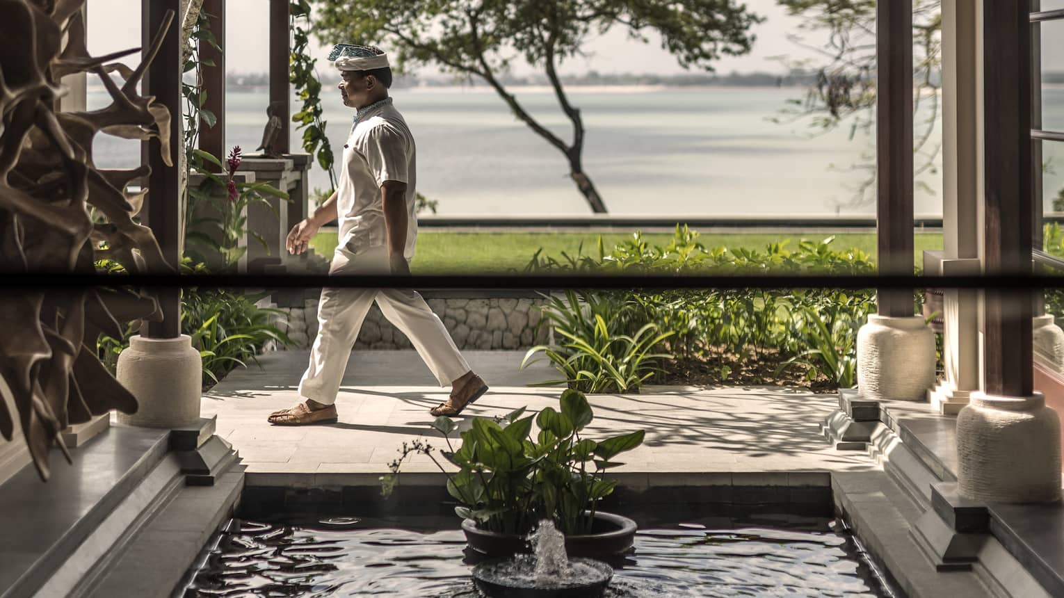 Man in white uniform walks by small pond on patio, green grass and beach in background