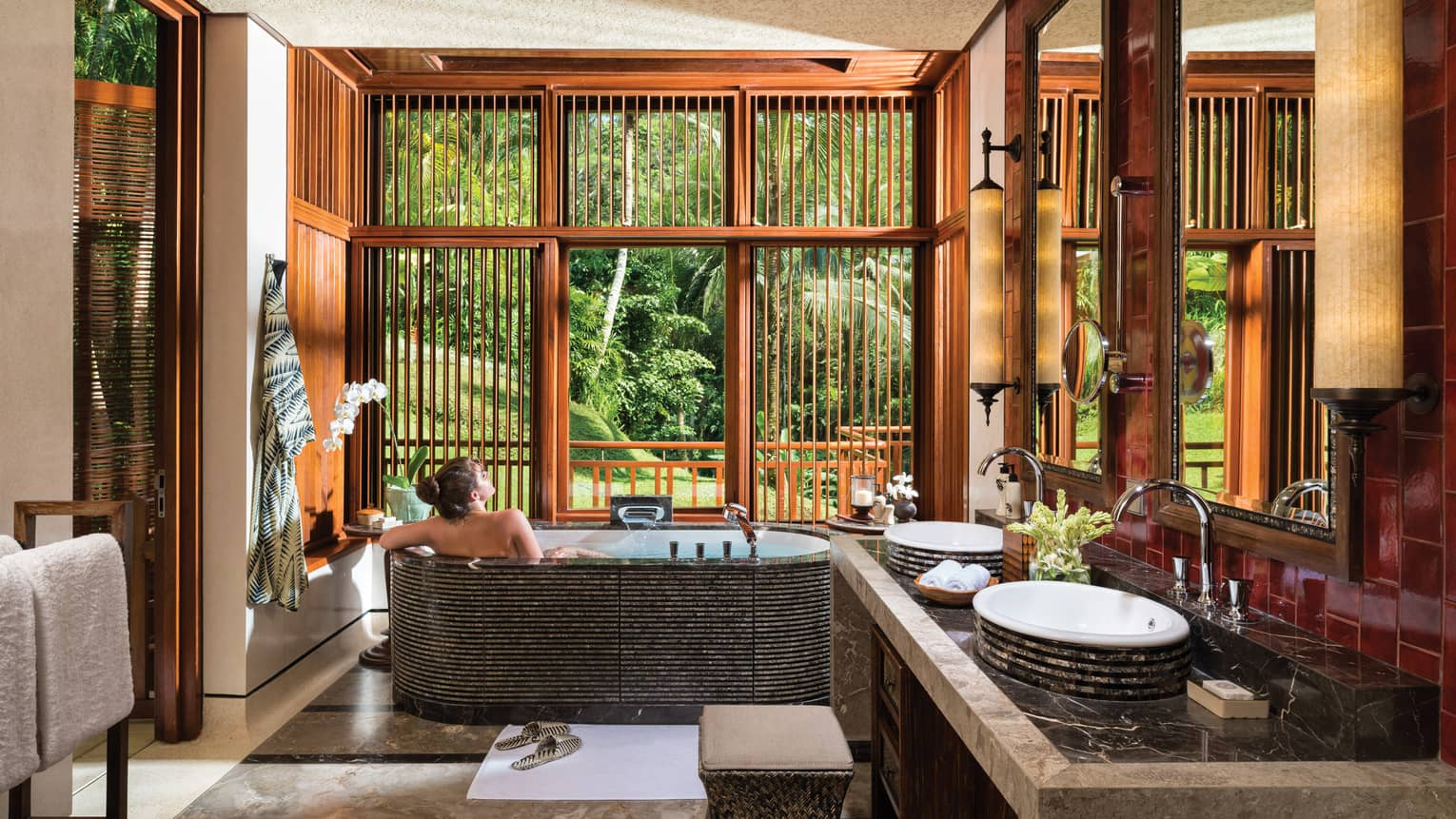 Woman with bare back relaxes in black freestanding spa tub near double sink, wood shutters open to lush garden view