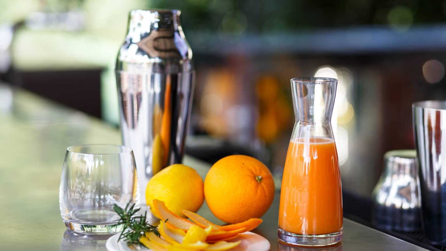 Orange Smoothie in glass jug on bar with fresh oranges, orange peels, stainless steel cocktail shaker