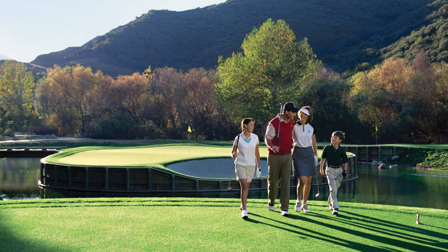 Family holds golf clubs, walks along sunny green on course near ponds, mountains