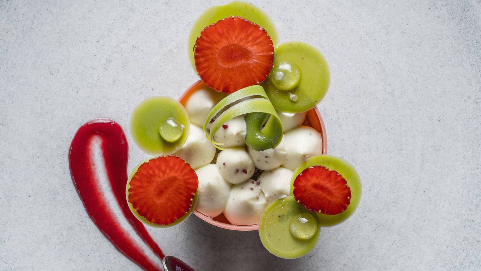 Artisanal dessert, small ice cream scoops garnished with artistic fruit slices, sauce