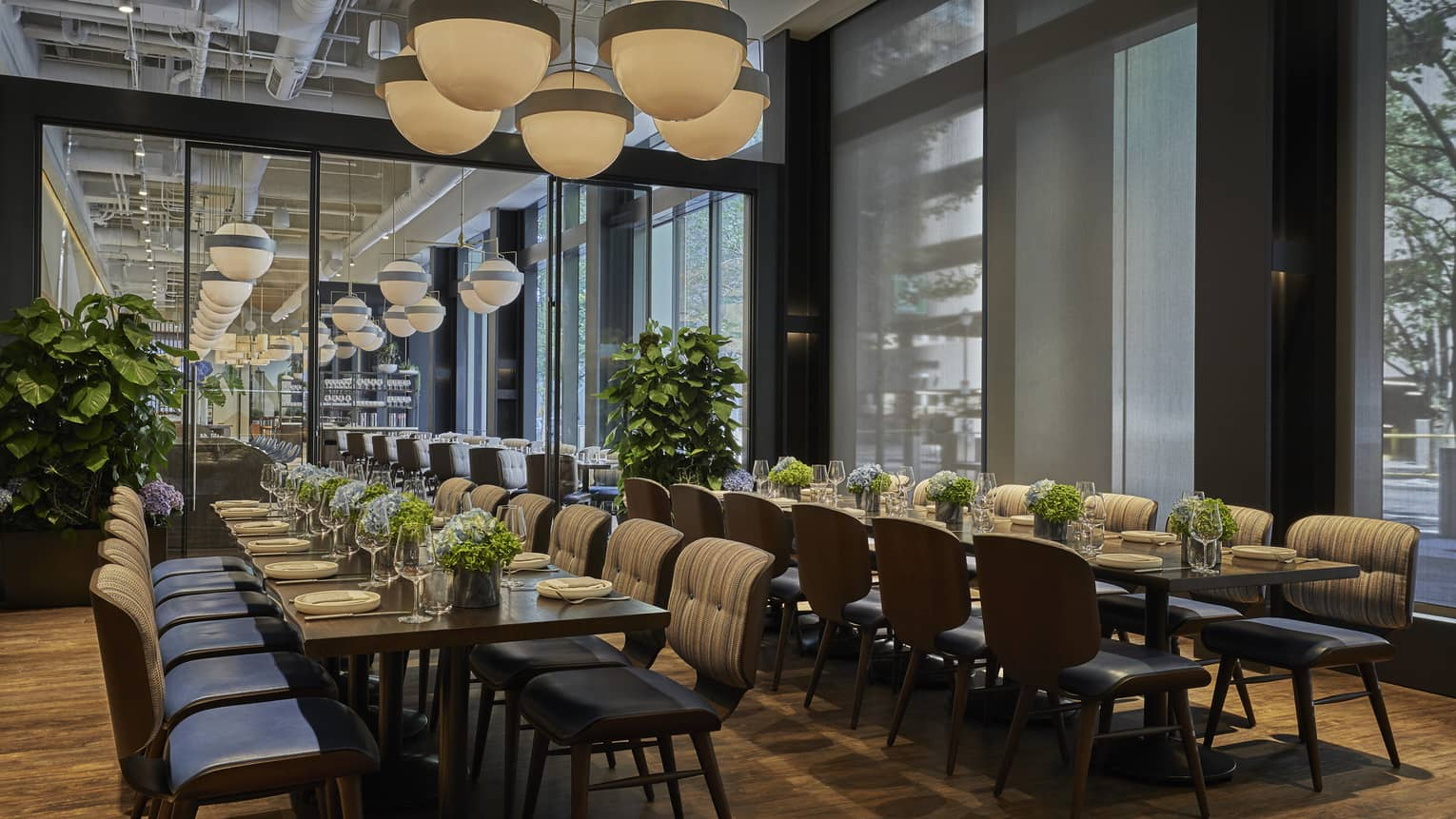 Two long tables are set with plates and white floral arrangements in Vernick Restaurant in Four Seasons Philadelphia