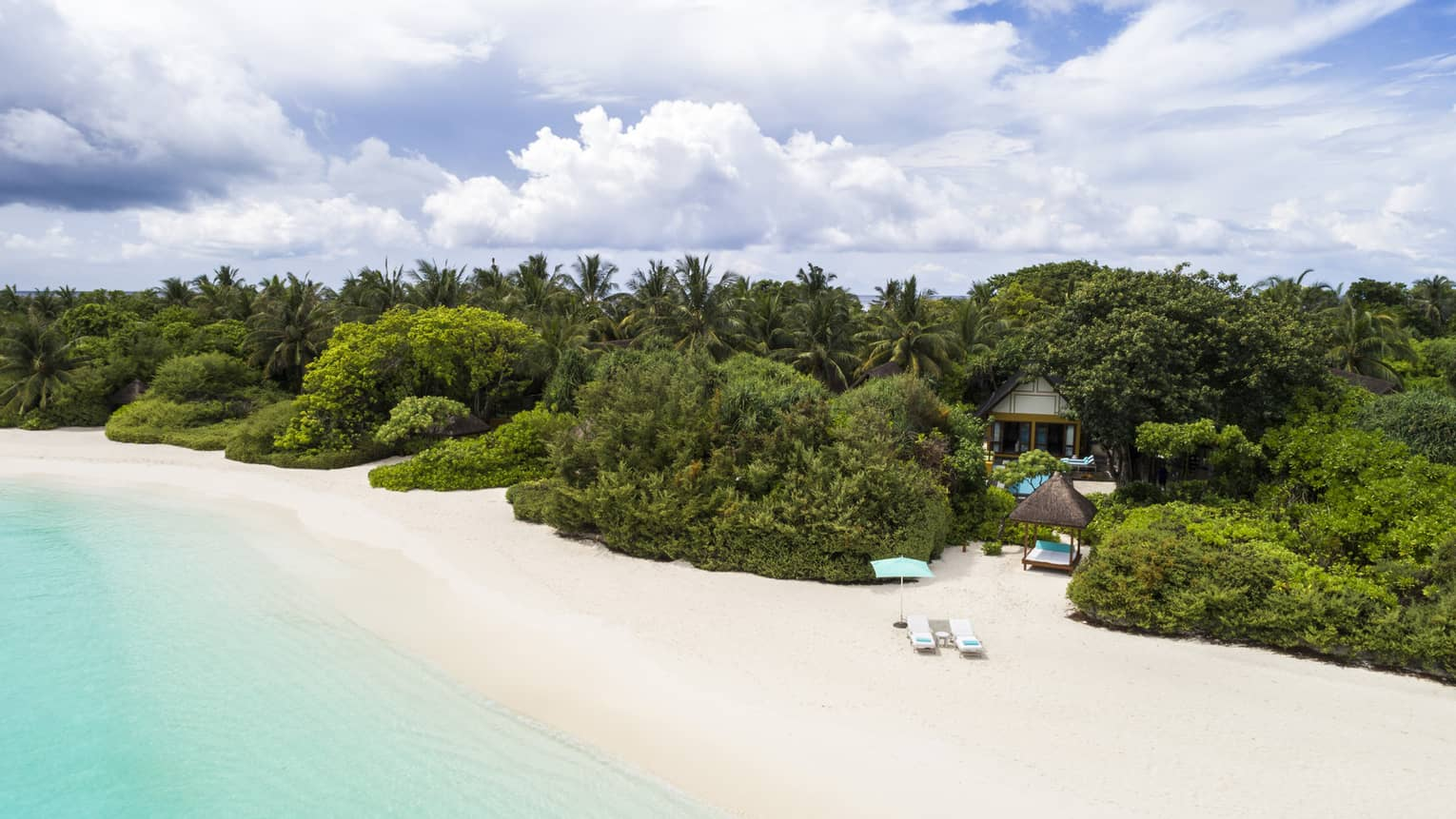 Quiet white-sand beach in the Maldives with turquoise water and lush green trees inland