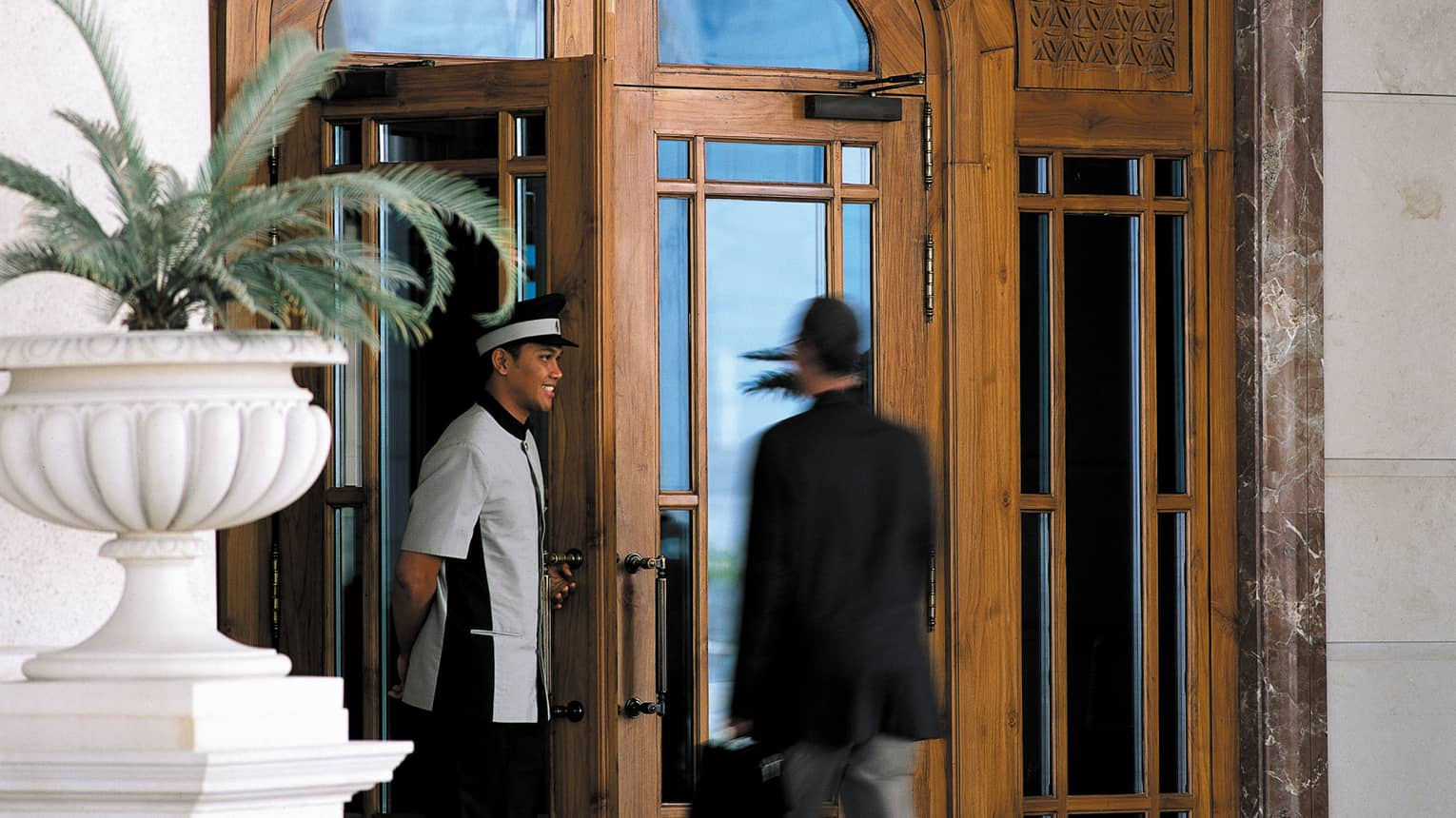 Smiling doorman opens door for guest at Four Seasons Doha hotel