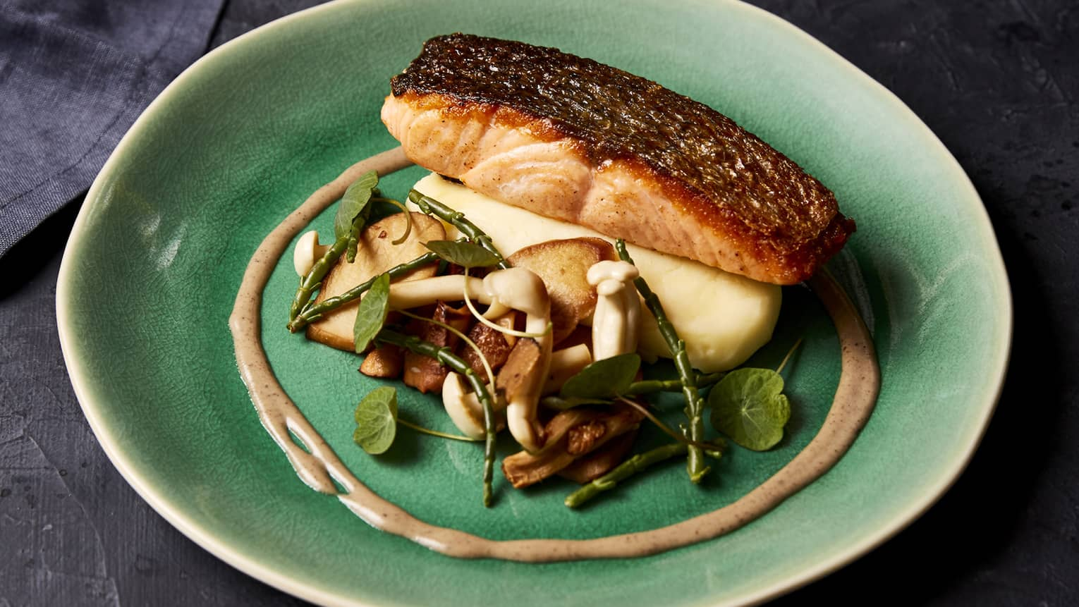 Blackened salmon with assorted mushrooms and greens on round green plate