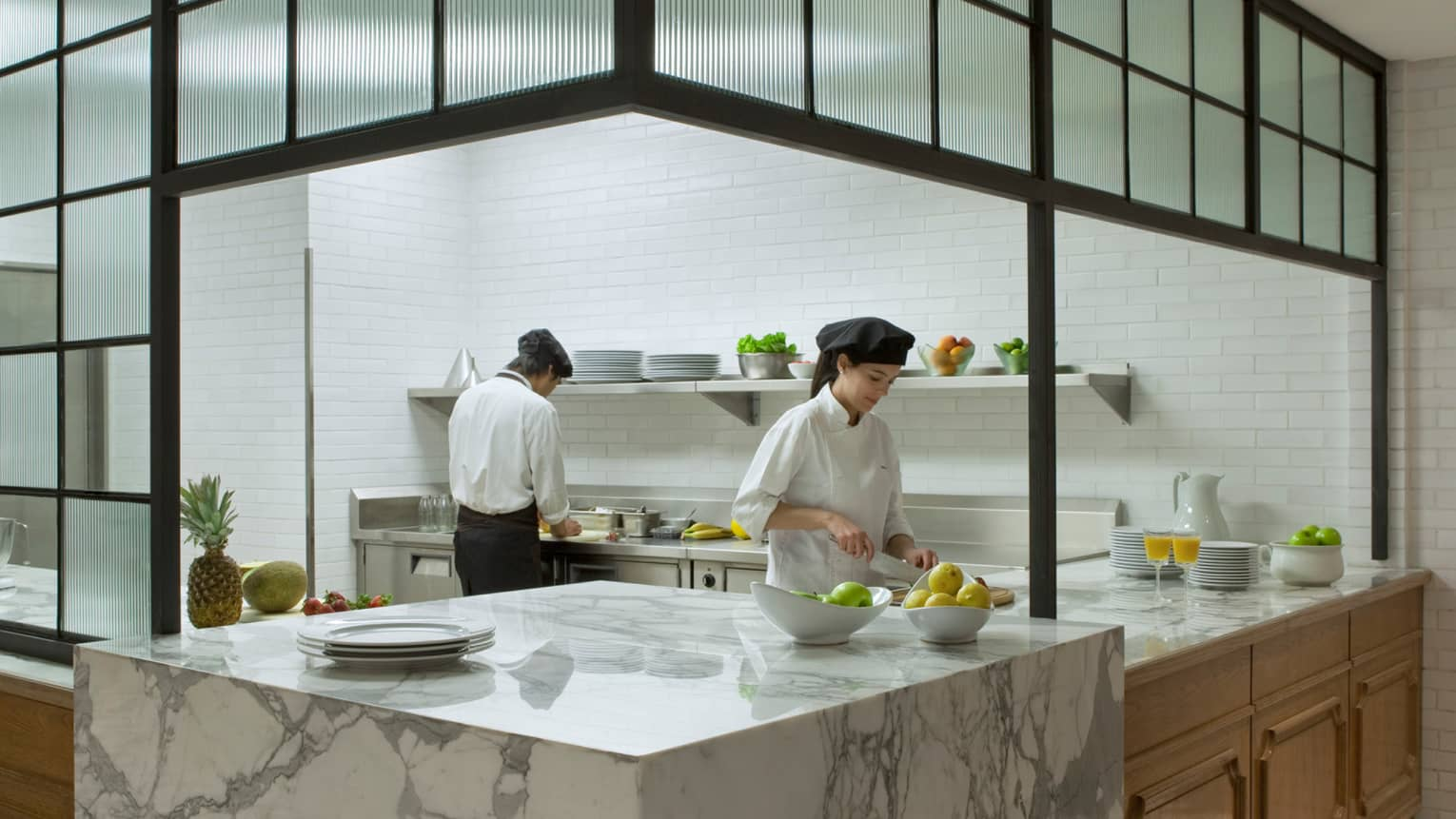 Two chefs work behind large grey-and-white marble counter with bowls of fresh apples, orange juice in glasses