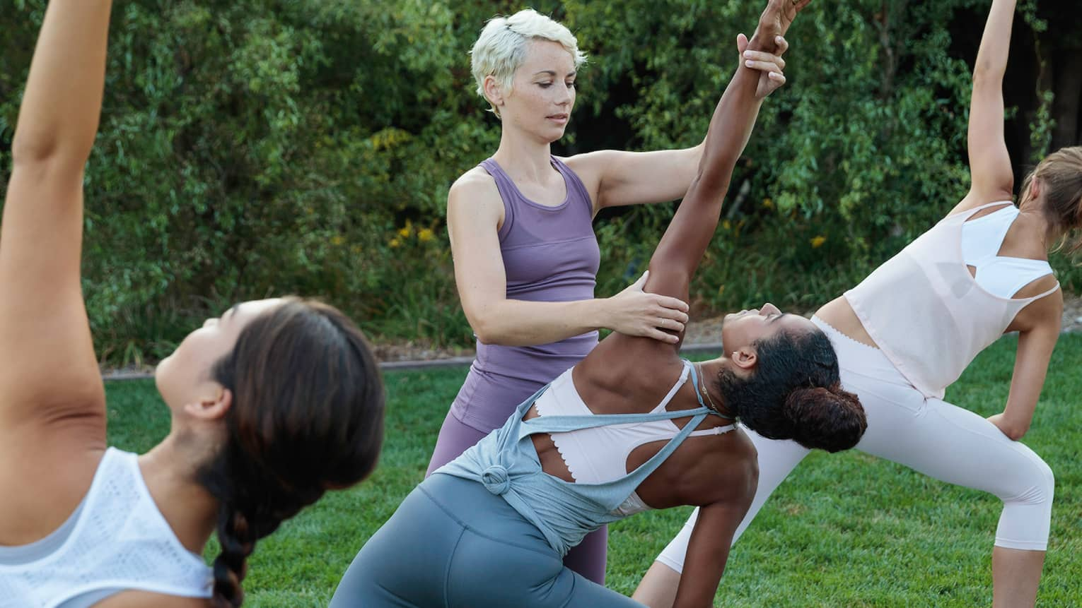 Fitness instructor assists woman with yoga pose on green lawn
