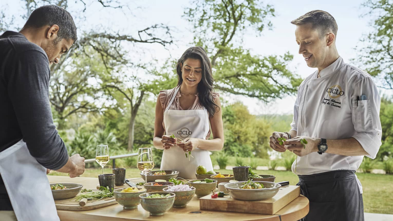 A four seasons chef guides a couple through an outdoor cooking class at four seasons hotel sydney